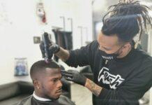 Il barbiere Wandy mentre taglia i capelli a Keita
